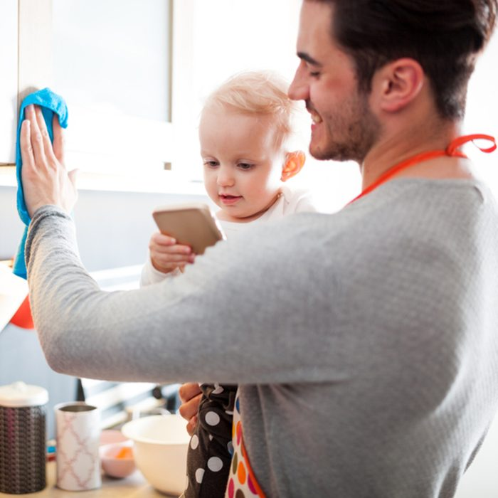 Modern Masculinity, young father with his little daughter on hand cleaning kitchen