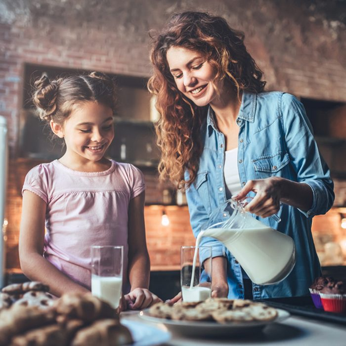 Attractive young woman and her little cute daughter are eating cakes and cookies on kitchen and drinking milk