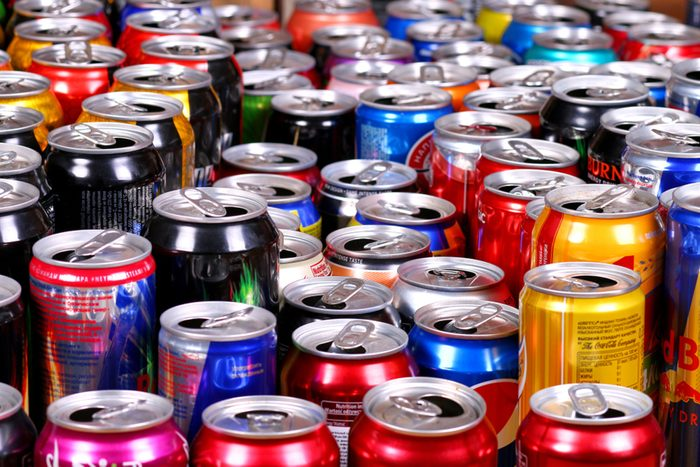 Many aluminium cans of sparkling drinks (Fanta, Sprite, Coca-Cola, Adrenalin Rush, Dr Pepper, Burn, Red Bull, Schweppes etc.) staying in rows.