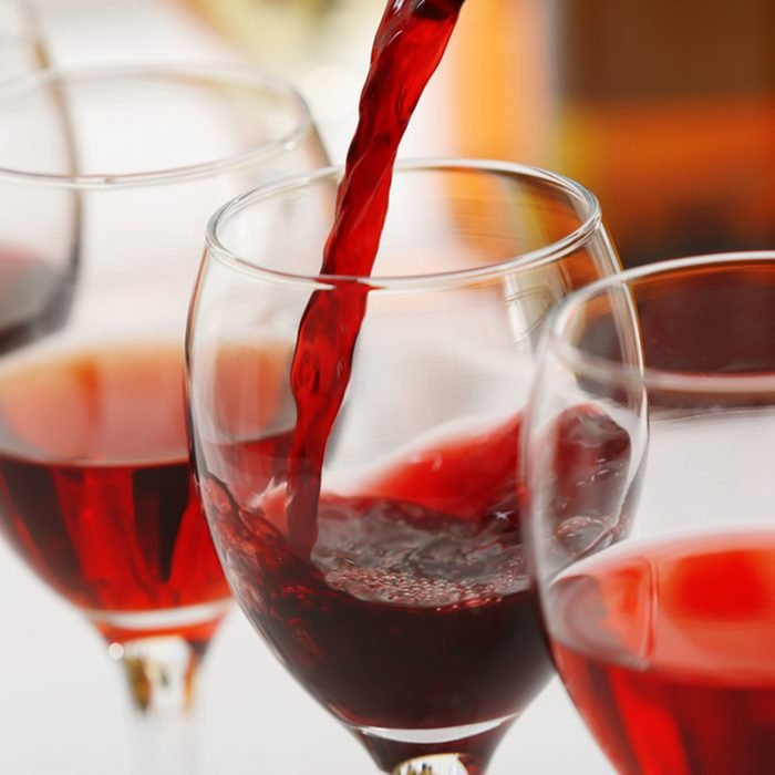 Red wine pouring into glasses