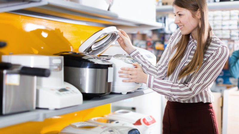 Young positive female housewife choosing multicooker in household appliances store
