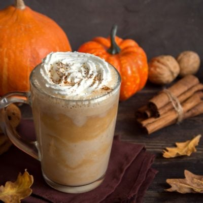Pumpkin Spice Latte. Cup of Latte with Seasonal Autumn Spices, Cookies and Fall Decor.