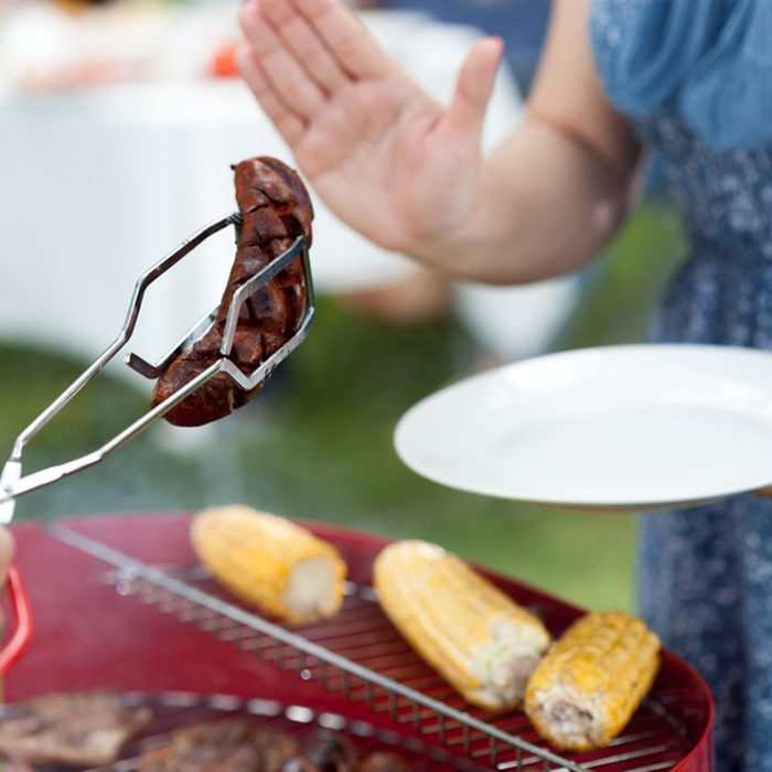 Woman refusing frazzled sausage on barbecue party