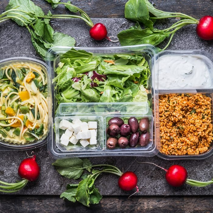 Variety of clean dieting salads in plastic package and green measuring tape on rustic background, top view.