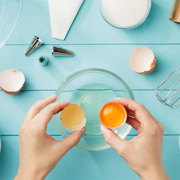 Female hands separate egg white from yolk for whipped cream. Step by step recipe of meringue with ingredients and utensils. Flat lay.; Shutterstock ID 1019679694; Job (TFH, TOH, RD, BNB, CWM, CM): -
