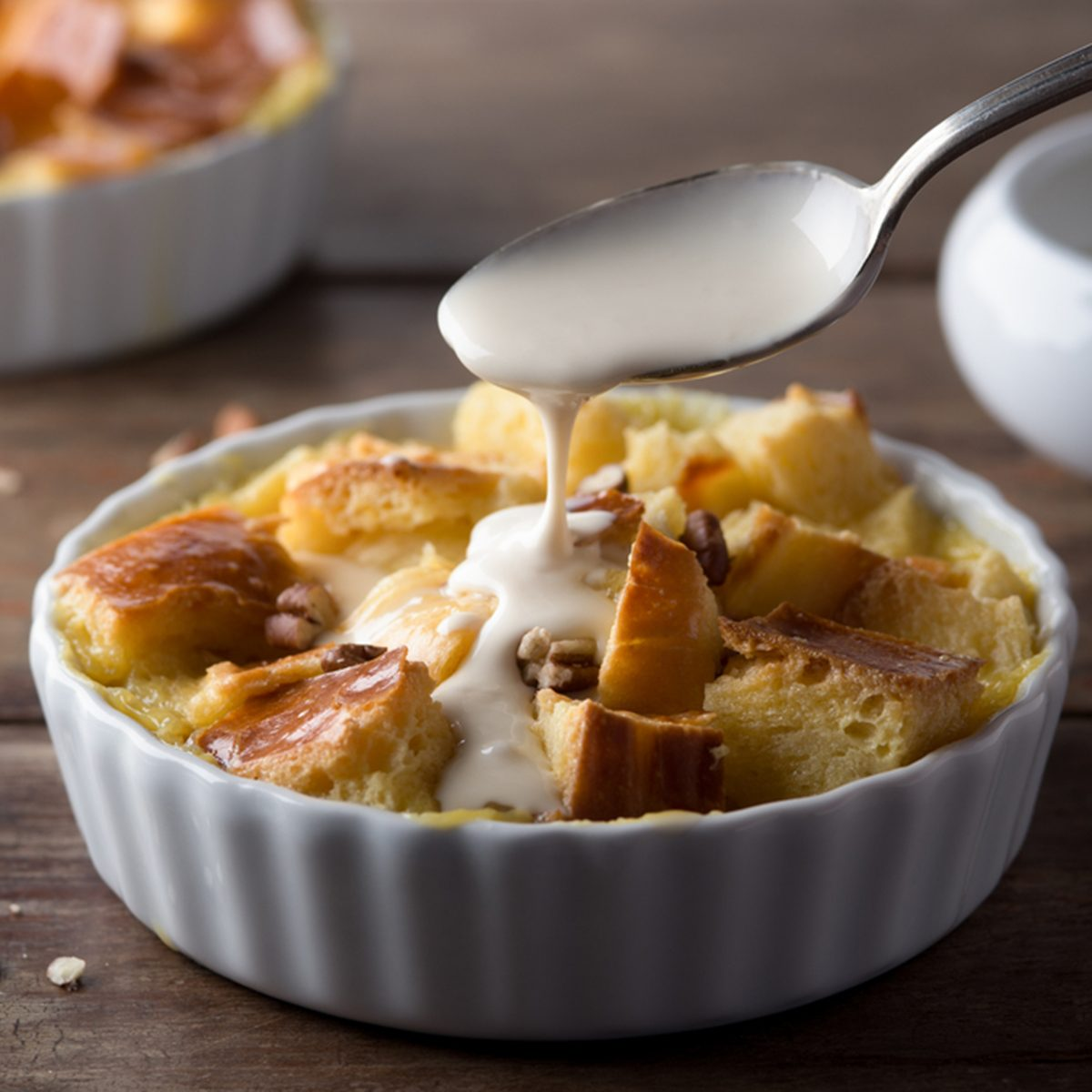 Pouring Maple Cream Sauce over Bread Pudding; Shutterstock ID 176583581; Job (TFH, TOH, RD, BNB, CWM, CM): Taste of Home