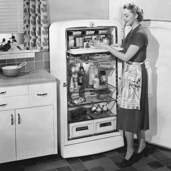 Woman with open refrigerator; Shutterstock ID 99385886