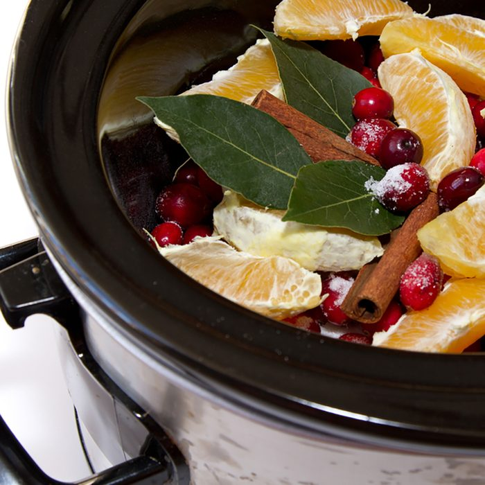 Homemade cranberry sauce ingredients of cinnamon, oranges, cranberries, bay leaf simmering in a crock pot isolated on a white background
