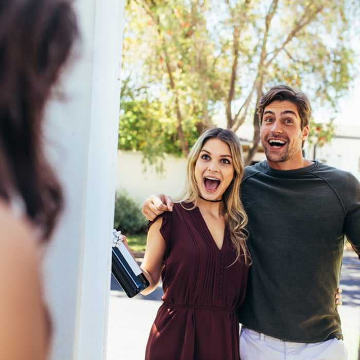 Excited couple at entrance door with bottle of wine.