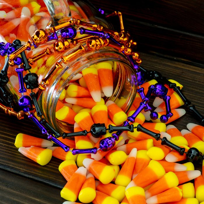 Halloween background of jar of candy corn and an assortment of voodoo bead on a dark wooden table.