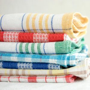 Pile of linen kitchen towels on a white background