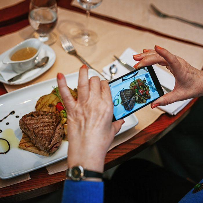 A Woman Taking A Photo Of Food On A Plate