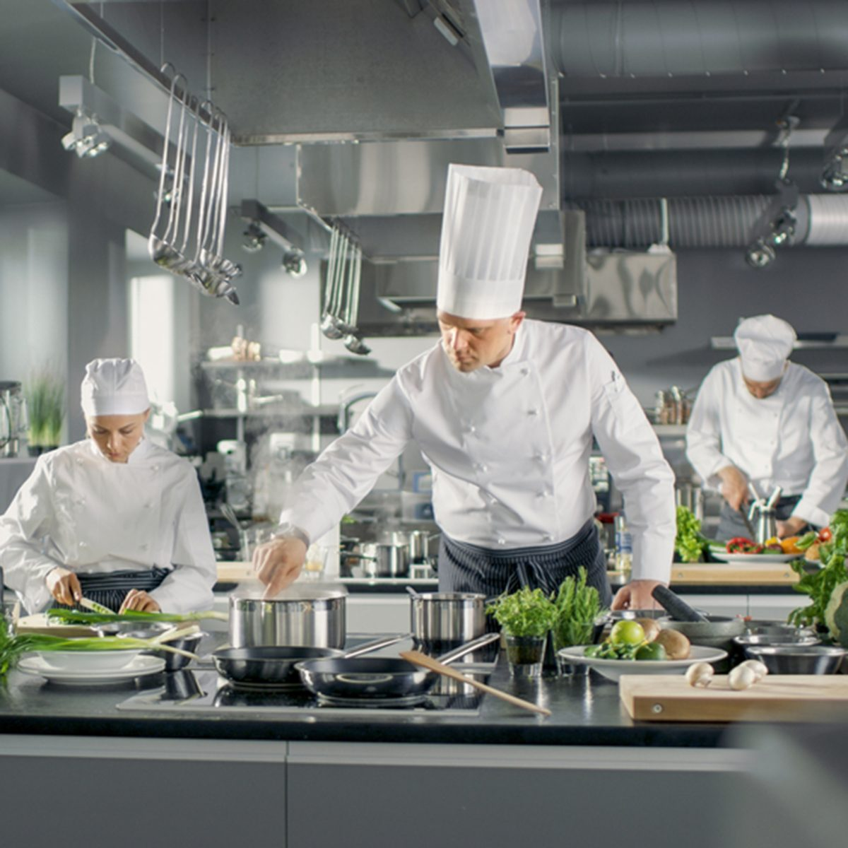 Famous Chef Works in a Big Restaurant Kitchen with His Help.
