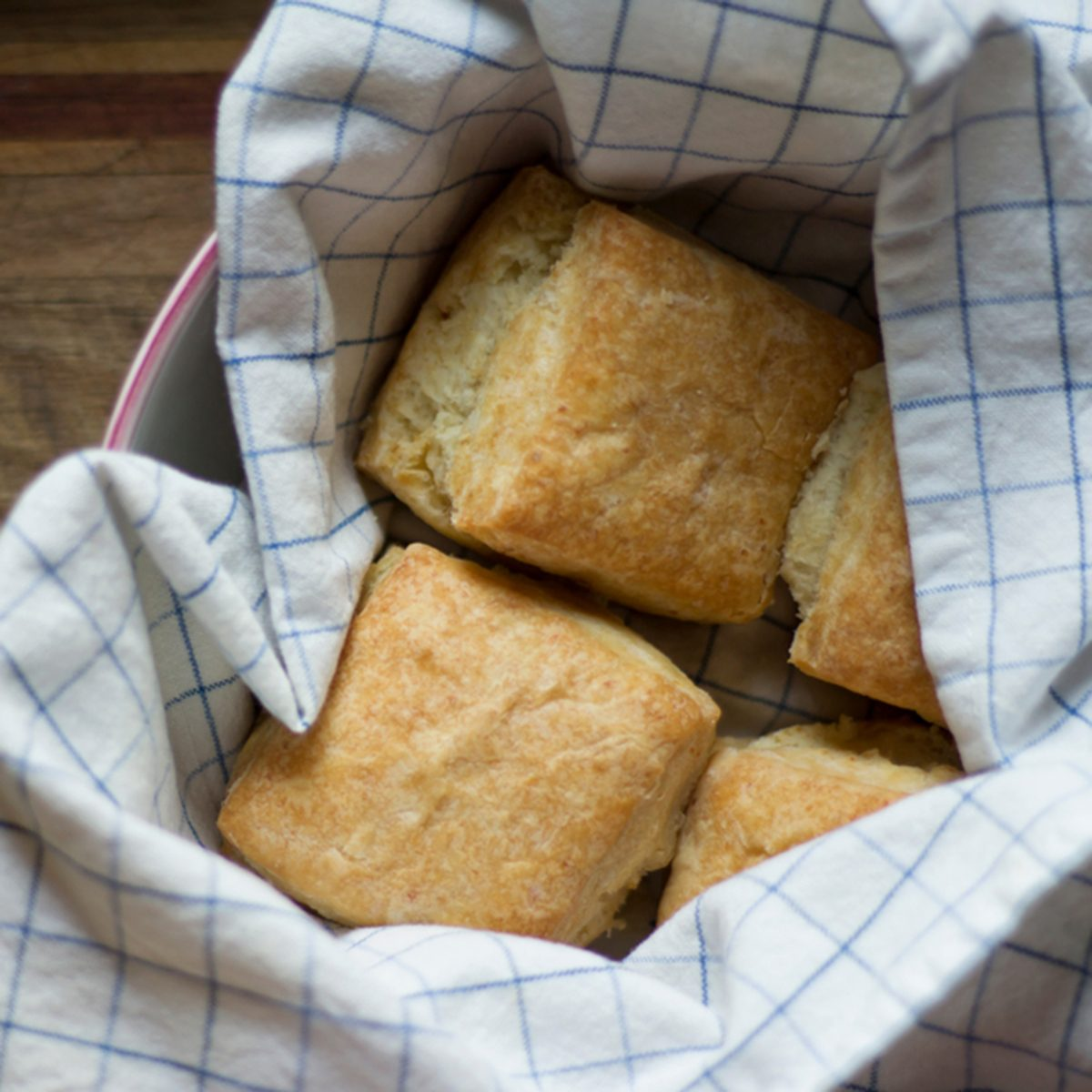 Freshly baked American biscuits in a kitchen towel and bowl