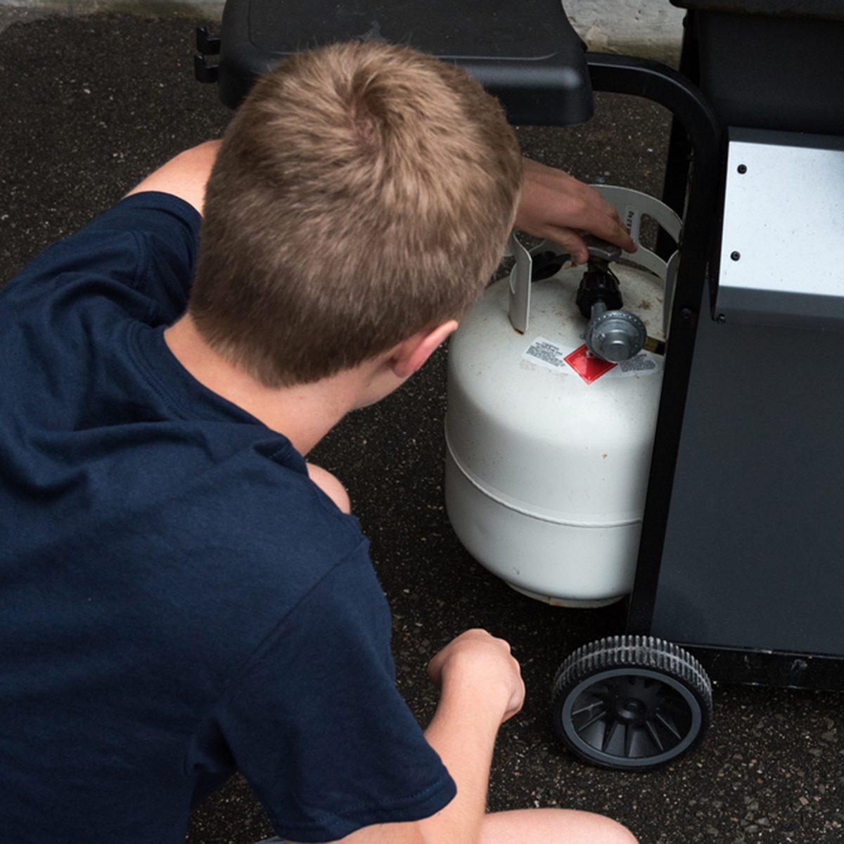 Teenager opening a propane tank for a barbecue