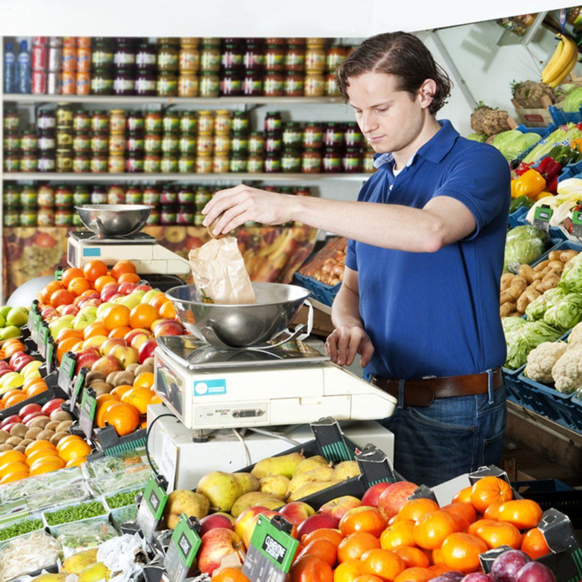 Greengrocer weighing fresh food on a digital scale