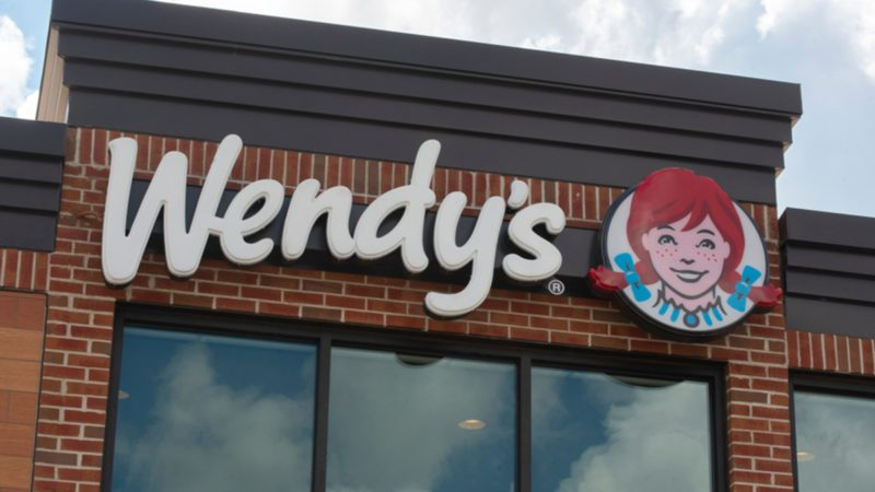 A Wendy's sign as seen from the outside of a retail location.