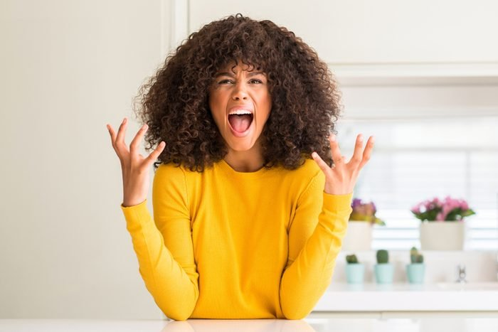 African american woman wearing yellow sweater at kitchen crazy and mad shouting and yelling with aggressive expression and arms raised.