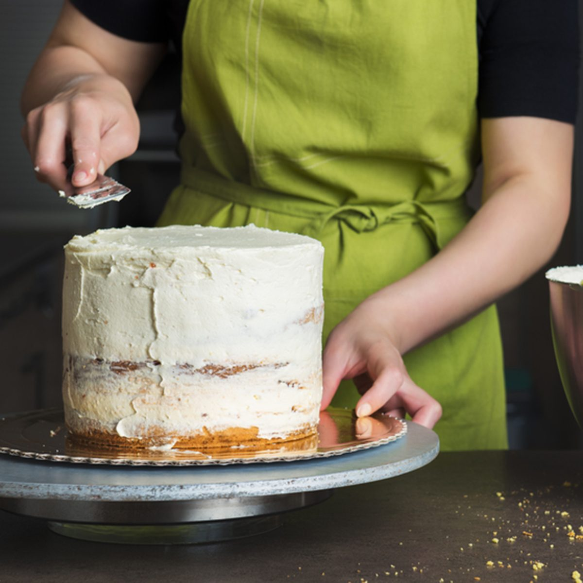 Unrecognizable woman decorating a delicious layered sponge cake with icing cream.