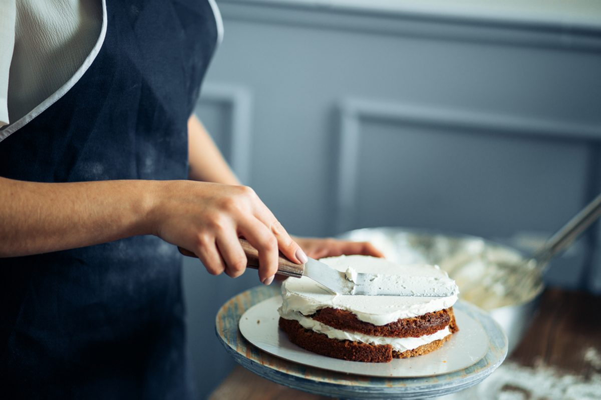Woman Carefully Icing The Cake And Decorating