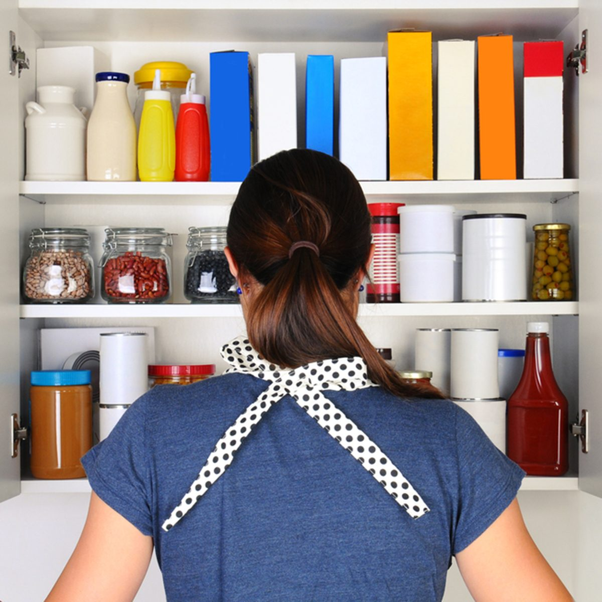 A woman seen from behind opening the doors to a fully stocked pantry.