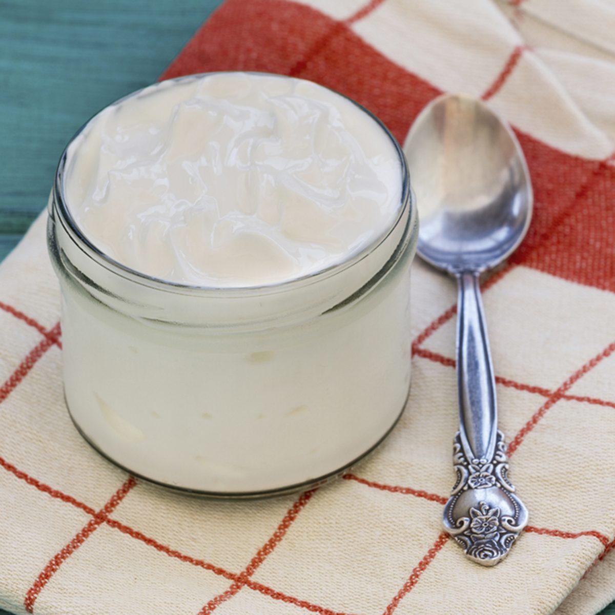 Greek Yogurt or Plain Yogurt and a spoon on a vintage wood background.