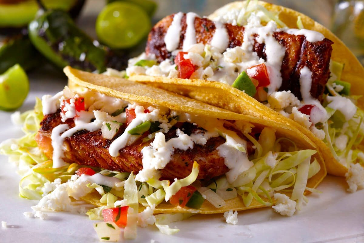 Grilled fish tacos with diced avocado and crema