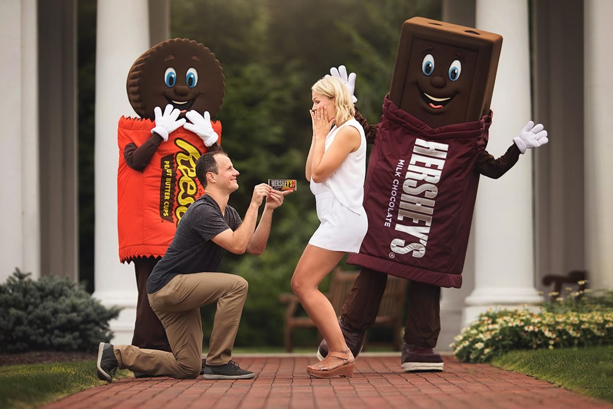 Craig Hirschey mock proposing to Jenny Ries with HERSHEY'S Milk Chocolate Bar with REESE'S PIECES candy in Hershey, PA long side the HERSHEY'S and REESE'S mascots.