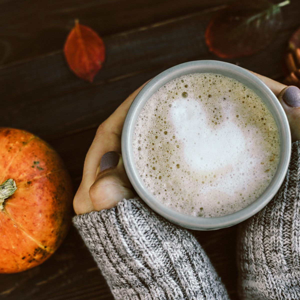 Cup of Spicy pumpkin latte in Woman's hands in gray sweater on the brown wooden table with red leaves. Cozy autumn mood; Shutterstock ID 472601899; Job (TFH, TOH, RD, BNB, CWM, CM): TOH