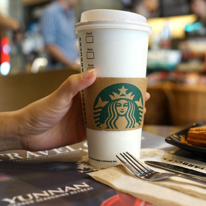 Close up female hand holding a cup of hot Starbucks coffee.