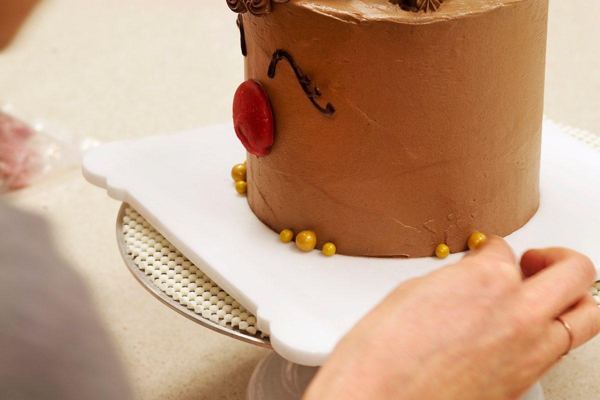 Putting gold balls on base of reindeer cake