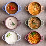 Assorted soups from worldwide cuisines displayed in bowls in three colorful lines garnished with cream and herbs