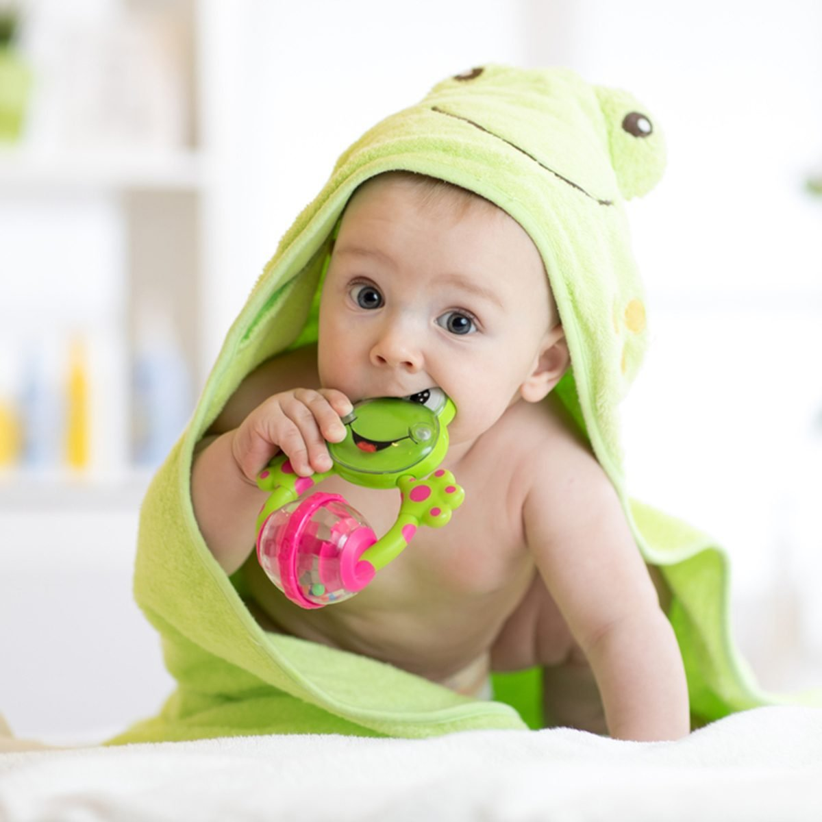 Baby boy with green towel after the bath biting toy.