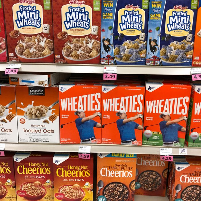 Several boxes of Cereal on a Grocery store shelf
