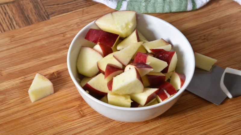 A bowl of diced apples on a cutting board