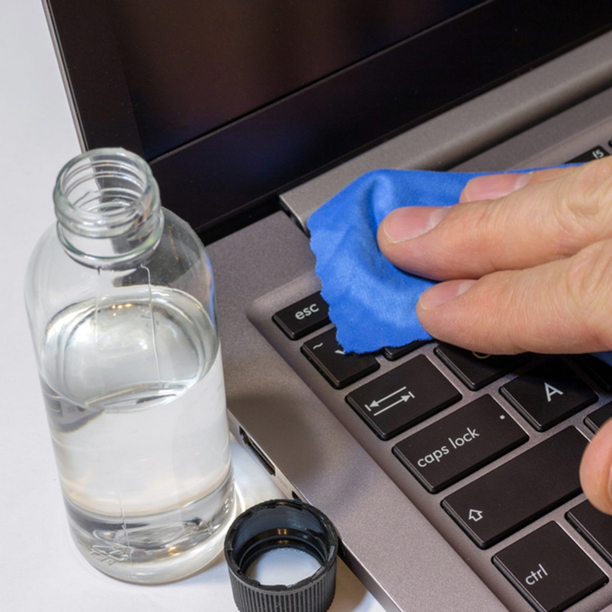Cleaning the surface of keyboard laptop with a blue rag microfiber