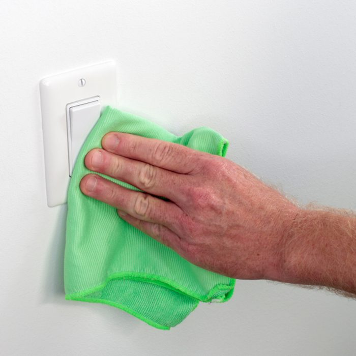 Persons hand wiping a wall white light control.