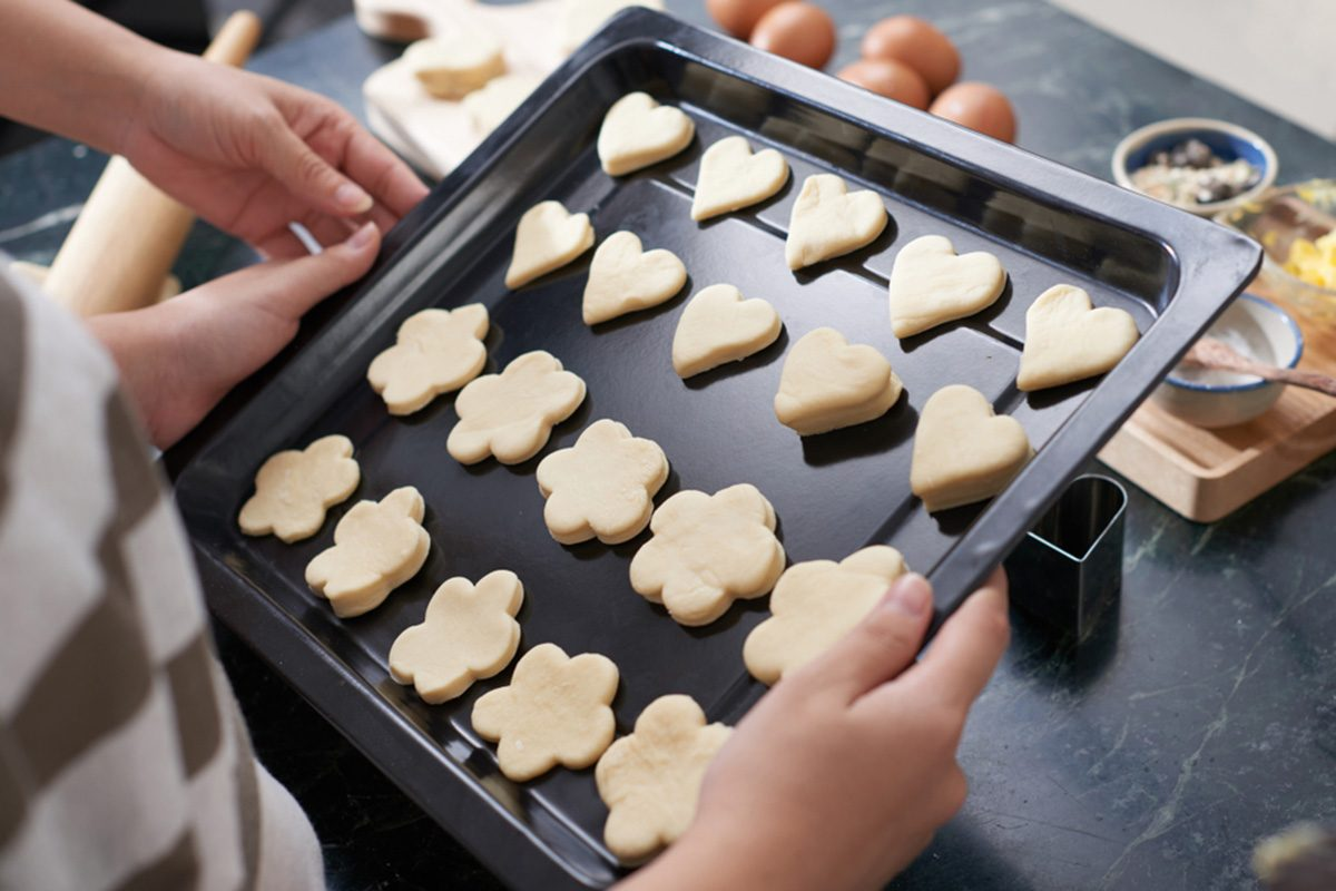 Close-up view of female hands holding baking sheet with cut out raw cookies of different shapes