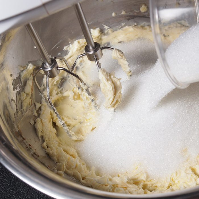 Mixing butter and sugar in bowl with mixing machine
