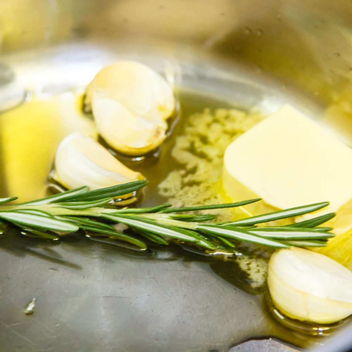 A sprig of rosemary and the garlic cloves are roasted with butter in the pan.