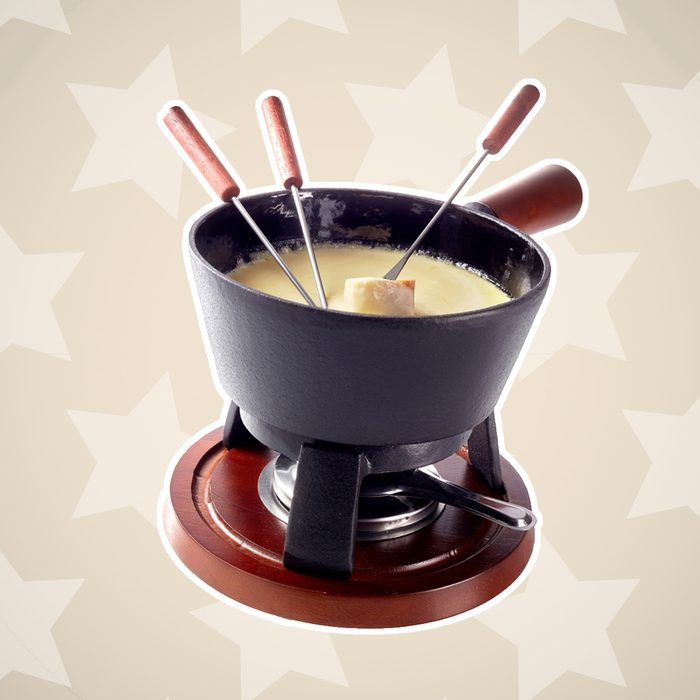 Isolated Swiss cheese fondue in a pot on a burner to keep the melted cheese and wine blend hot with long handled forks and bread for dipping; Shutterstock ID 484573432; Job (TFH, TOH, RD, BNB, CWM, CM): TOH