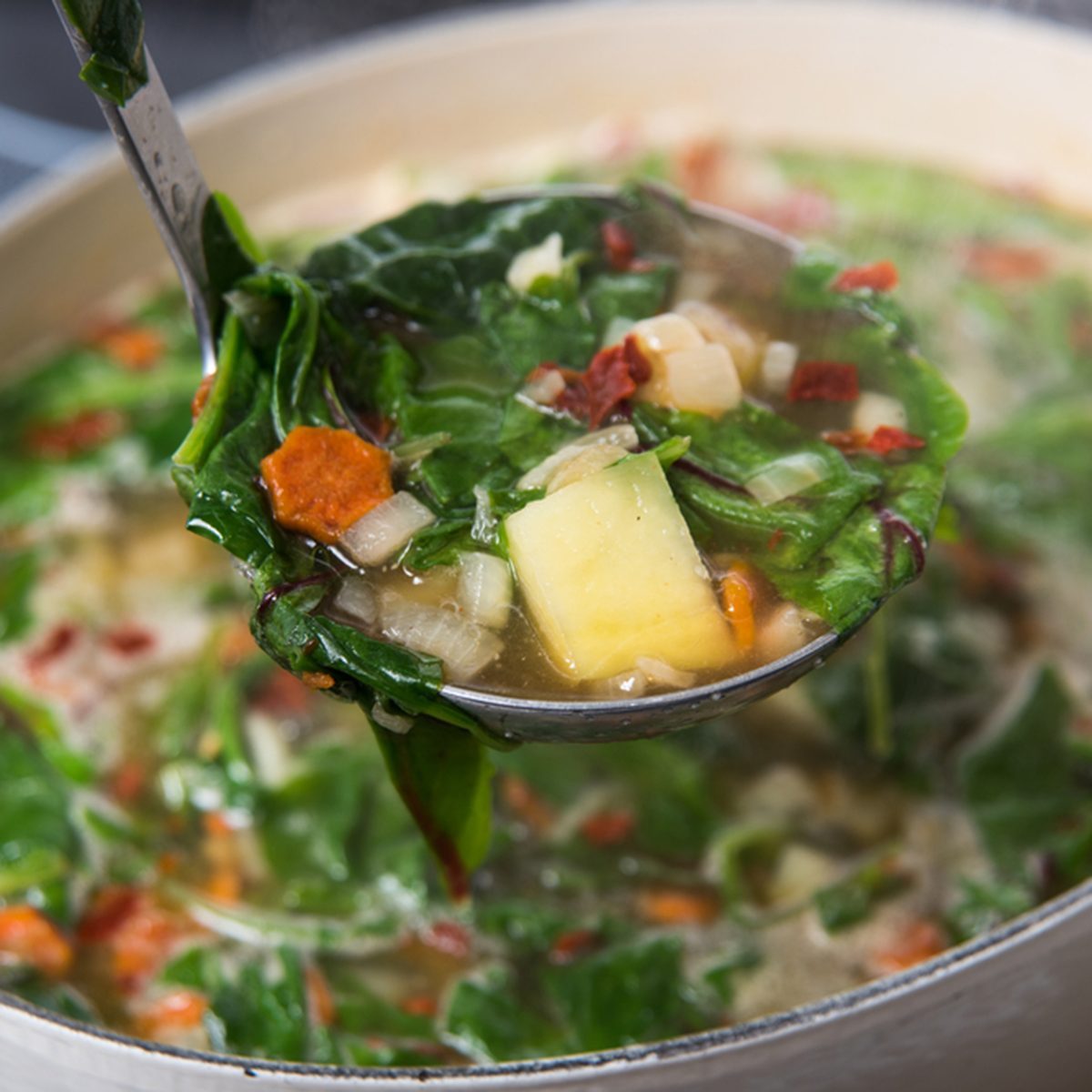 Making Fresh Soup with Baby Greens, Vegetables, and Chicken Bone Broth