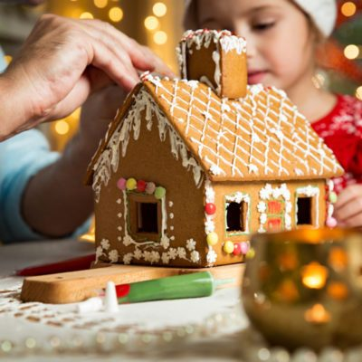Father and adorable daughter in red hat building gingerbread house together.
