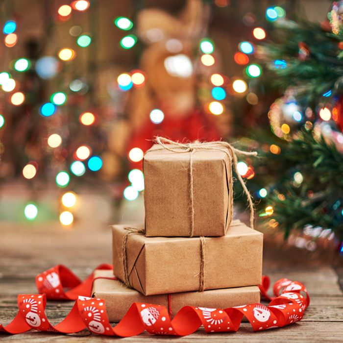 Gift boxes with a large red bow against a background bokeh of twinkling party lights.