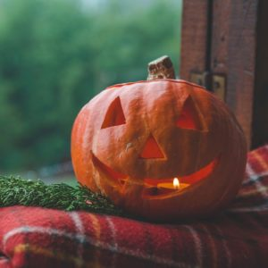 Background Halloween pumpkin on a cozy window sill with a red plaid. Whole pumpkin and sparkler outdoors.