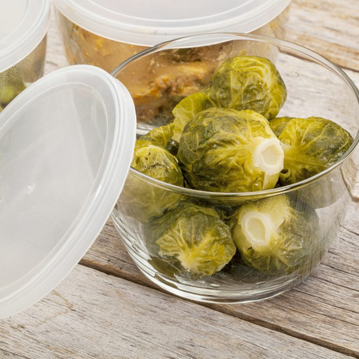 dinner meal or leftovers (chicken, brussels sprouts, asparagus, green pea) stored in glass containers