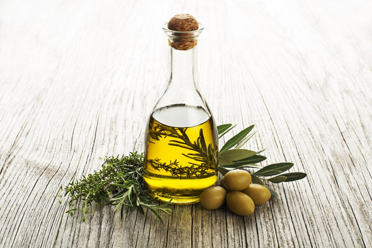 Olive oil with fresh herbs on wooden background.
