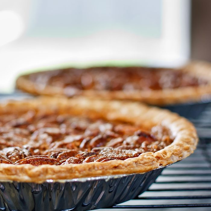 Pecan pies cooling on a rack in front of a window