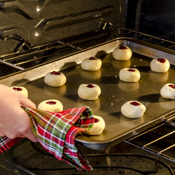 Pan of raspberry thumbprint cookies sitting on baking sheet being placed in oven to bake