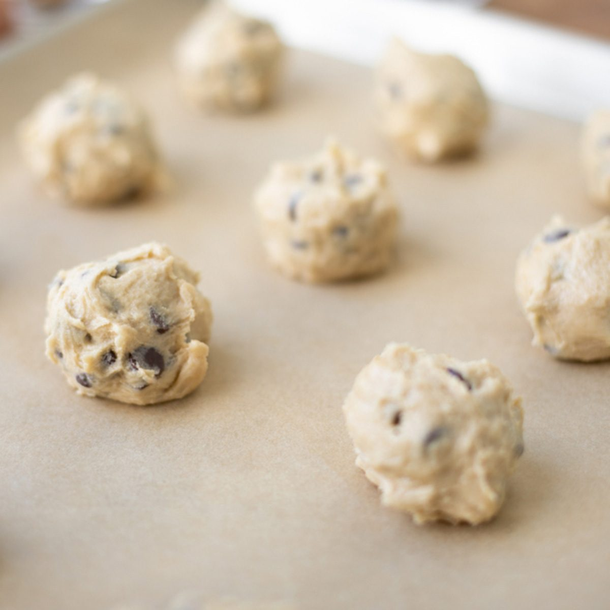 Close up on rows of chocolate chip cookie dough balls on a parchment paper lined baking sheet